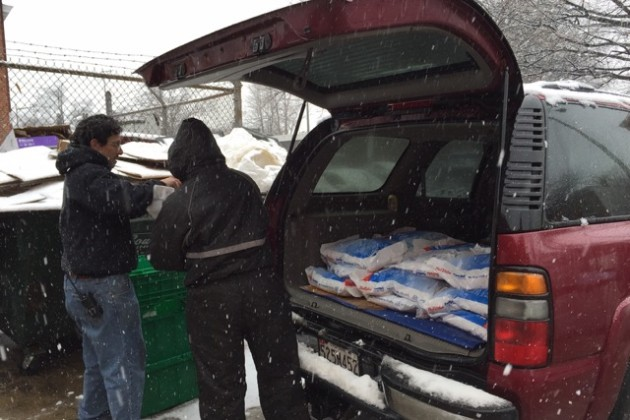 Frager's Hardware workers William Scheiman (left) and Andrew Melendy load ice melt into a car.