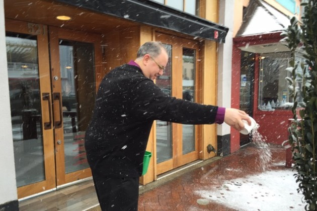 Matchbox general manager Jason Nichols spreads some ice melt in front of the restaurant.