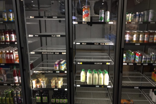 A nearly-empty refrigerator inside the store.